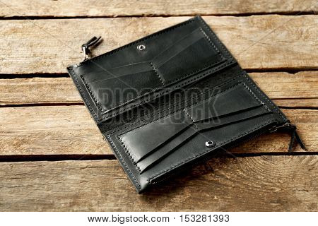 Black leather empty opened purse on wooden background