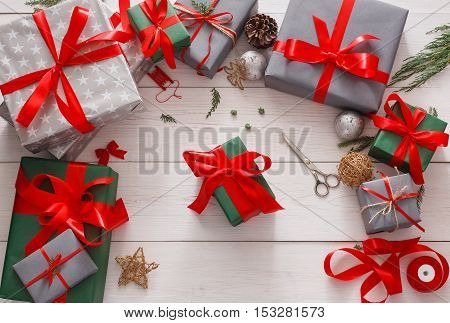 Lots of gift boxes on white wood background. Stylish modern presents in gray and green paper decorated with red satin ribbon bows. Christmas and winter holidays concept, top view, flat lay