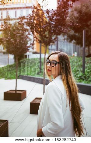 Attractive young woman with long hair is wearing stylish glasses and white suite and  walking on the background of urban buildings. Business people concept