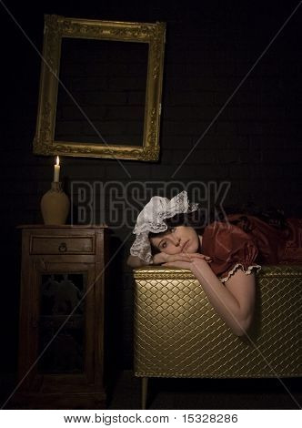Woman wearing vintage clothing and mop,lying down on a gold chest, vintage ornate frame on a brick wall, candle light