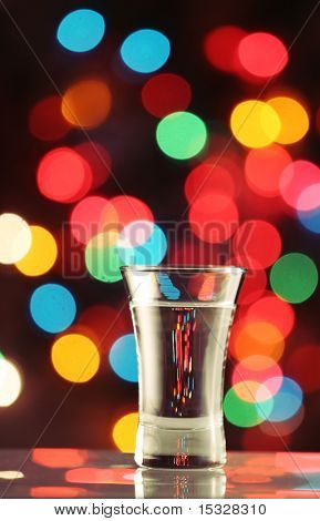 Shot glass with a see through liquid/vodka, fairy light background please check for more