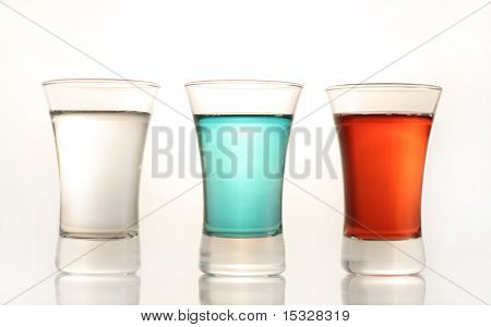 Three shot glasses with red, blue and see through liquid