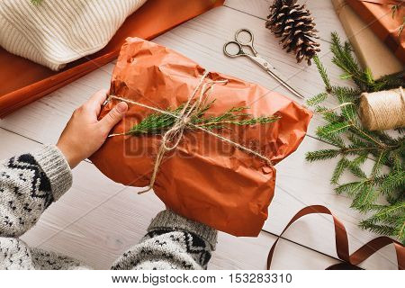 Gift wrapping background. Female hands packing sweater as christmas present in maroon paper decorated with satin ribbon. Winter holidays concept. Top view of white wood table with fir tree branches