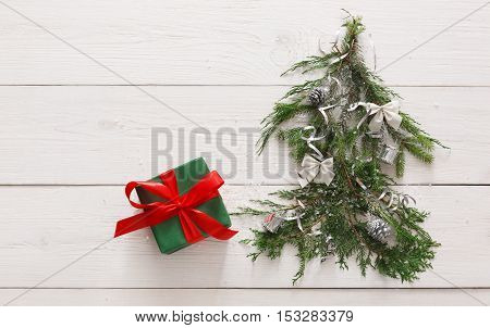 Christmas background. Gift boxes on fir tree branches at white wood. Stylish modern present in green paper decorated with satin ribbon bows. Winter holidays concept, top view, copy space