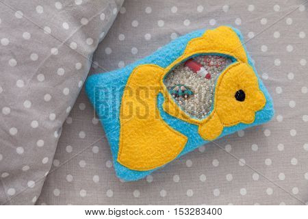 Children's soft toy goldfish made of colored fleece for motor development. Bag fleece filled with plastic beads and figurines on a background of gray fabric in white peas. handmade toys. Happy childhood.