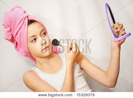 Cute young girl with a pink towel on her head, make-up brush and a mirror. Please check for more.