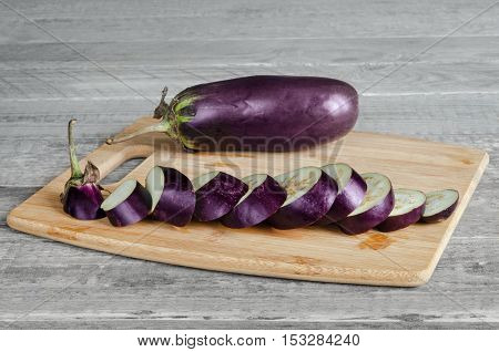 Eggplant lay on a cutting Board, on a gray wooden background.