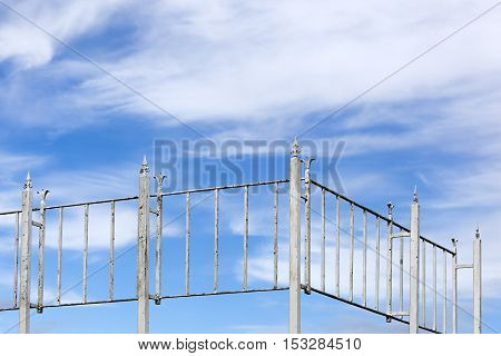 Vintage rusty white metal fence and a blue cloudy sky