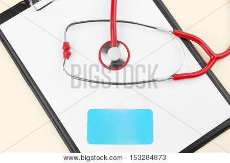 Stethoscope and business card on clipboard, closeup