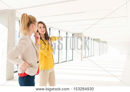 Young businesswoman discussing with female colleague in empty office