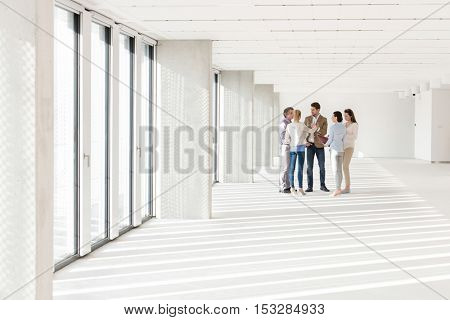 Full length of business people discussing in empty office