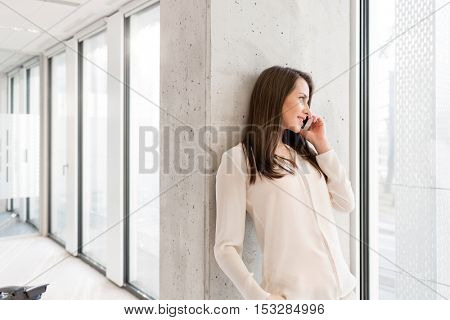 Young businesswoman using mobile phone while leaning on wall in new office