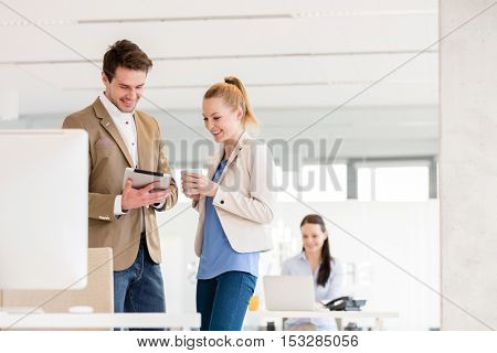 Young businesswoman with male colleague using digital tablet in office