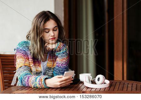 Woman In Woolen Sweater Uses A Smartphone On Terrace.