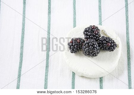 Four blackberries on the goat cheese and white towel with green stripes