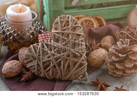 Composition of wicker heart and natural decor on wooden background, close up view