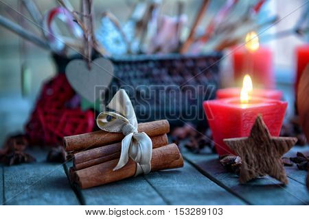 Composition of cinnamon sticks, candle and star on wooden background