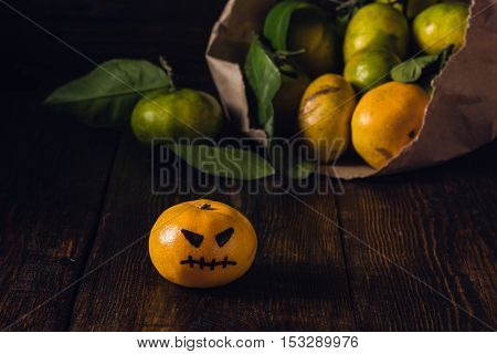 Scary tangerines for Halloween and bunch of tangerines on background