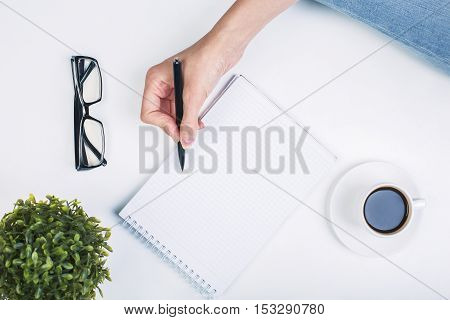 Top view of businesswoman's hand writing in notepad placed on white surface with coffee cup and other items. Mock up