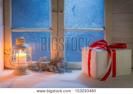 Frosted window with burning candle for Christmas at night