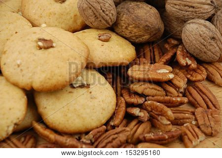 Background  for autumn, winter holidays, with cookies, walnuts and pecan nuts on a wooden texture table. Christmas table, morning