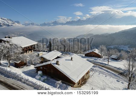 Morning in the mountains, in Cordon, Haute-Savoie department in the Rhône-Alpes region in south-eastern France, with snow covered cabins and roads in the front and the Alps in the back.