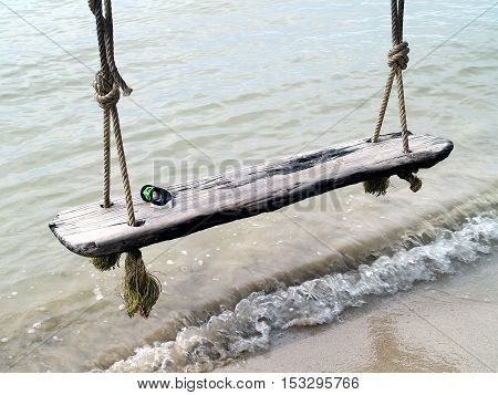 Swimming goggle on old wood swing over the waves on the beach at Koh Chang, Thailand, relaxation by the sea