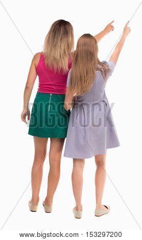 Back view two pointing young girl. Rear view people collection.  backside view person. beautiful woman friends  showing gesture. Isolated over white background. Two girls show his hands to sky