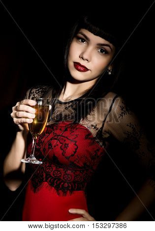 Young celebrating woman in a red dress holding a glass of champagne.