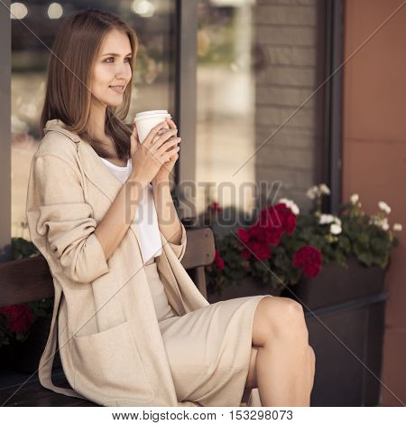 Young stylish woman sitting on bench and drinking coffee.