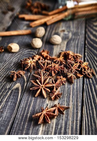 Heap of anise stars on wooden table. Aromatic spice for Christmas drinks, mulled wine or gluhwein and desserts. Widely used in cooking, perfumery and medicine. Delicious flavor. Selective focus