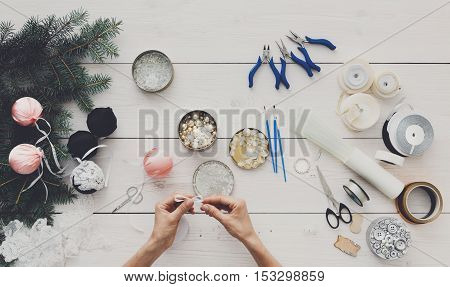 Making handmade christmas balls. Woman's leisure, tools for creating holiday decorations and garland. Top view of white wooden table with female hands holding various trinkets, decor accessories