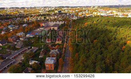 Street in auntumn in town near park by drone