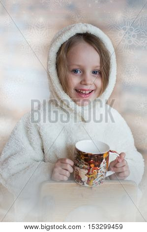 portrait of a beautiful little girl with a mug in his hands. Christmas symbols on a mug.