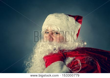 Santa Claus Carries A Bag With Gifts.