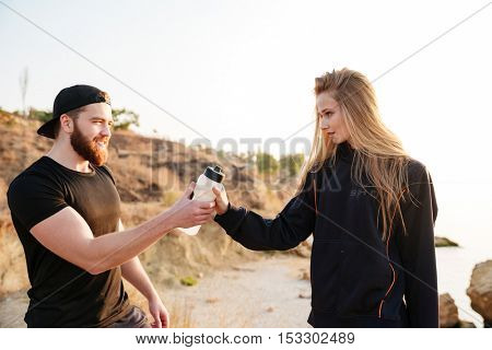 Healthy man and woman resting after training and drinking water outdoors at the beach