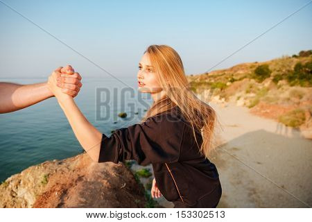 Cropped image of a man hand helping woman to climb a hill at the seaside