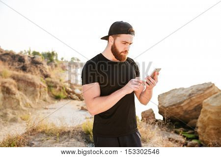 Handsome young bearded sportsman standing and using cell phone on the beach