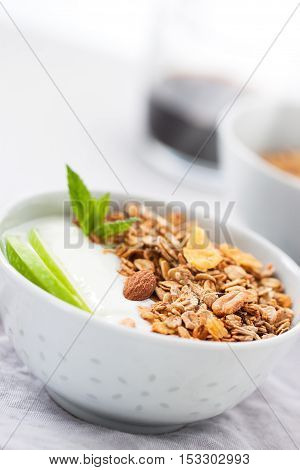 Granola with yogurt and apples in a bowl for breakfast closeup