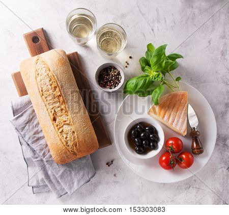 Italian appetizers view from above - bread ciabatta olives tomatoes cheese pepper fresh basil and wine ready for cooking