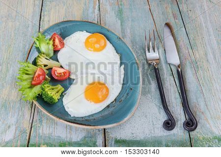 Breakfast consists of fried eggs and vegetables on the old wooden table rustic style