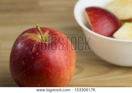 Blick auf einen Apfel neben neben einer weißen Schale auf einem Holztisch.