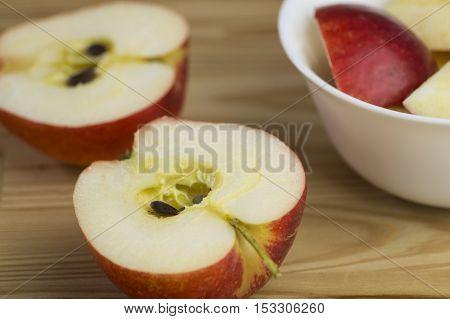 Halbierte Äpfel auf einem Holztisch zur kalten Jahreszeit. Vitaminreiche Ernährung