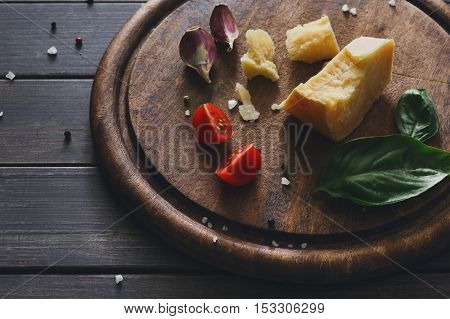 Cheese delikatessen baclground, closeup on rustic wood. Wooden desk with parmesan cuts decorated with garlic, tomato and basil