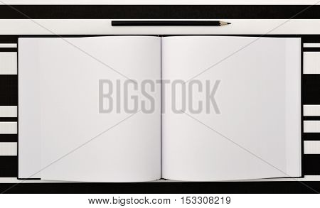 high-angle shot of a black pen and an open notepad with blank pages on a black and white surface