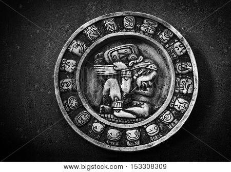 Carved circular Mayan calendar on textured background