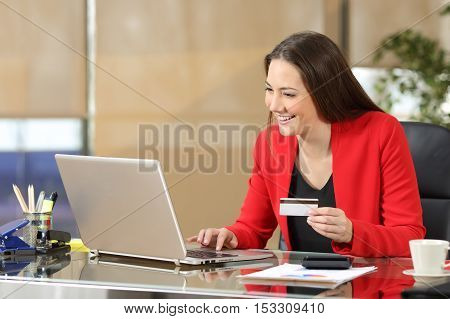 Portrait of a businesswoman wearing red suit buying on line with a credit card in a laptop sitting in a desk at office