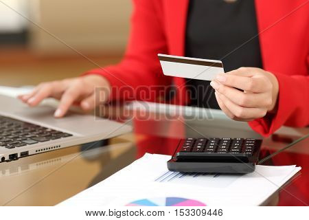 Businesswoman hands buying on line holding a credit card and entering data in a laptop sitting in a desktop at office