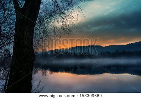 Reflection of trees from the water. Foggy sunrise. Autumn landscape on the lake.Tranquil landscape of misty swamp.Little island with trees. Mirroring the country from the river.
