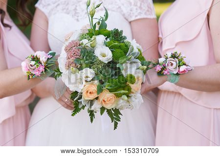 bride with bridesmaids are holding wedding bouquets.
